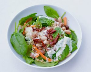 Bean and Quinoa salad complimented with spinach, topped with a lemon & garlic yogurt dressing..